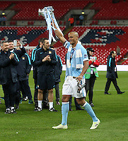 Vincent Kompany of Manchester City holds the Capital One Cup aloft after victory against Liverpool after the Capital One Cup match between Liverpool and Manchester City at Wembley Stadium, London, England on 28 February 2016. Photo by David Horn / PRiME Media Images.