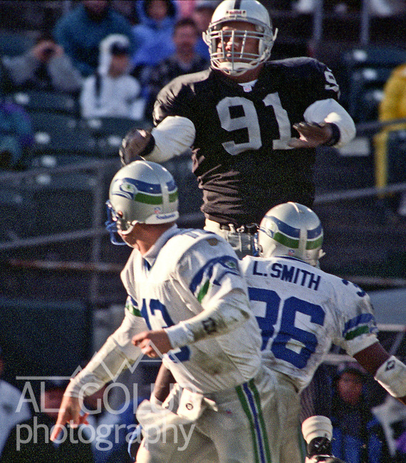 Oakland Raiders vs. Seattle Seahawks at Oakland Alameda County Coliseum Sunday, December 22, 1996.  Seahawks beat Raiders  28-21.  Oakland Raiders defensive tackle Chester McGlockton (91) jumps up t block view for Seattle Seahawks quarterback Gino Torretta (13).