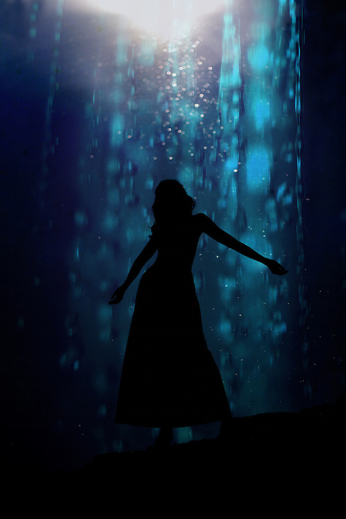 The silhouette of a young woman dancing against a blue background