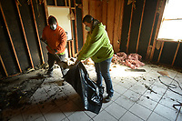 NWA Democrat-Gazette/ANDY SHUPE<br /> Timothy and Valerie Wright work together Saturday, Jan. 6, 2018, to shovel water-soaked insulation inside their living room after a fire heavily damaged their 1930s-era home Christmas Eve in Cincinnati. A temporary tarp roof is protecting the home as trusses are being constructed.