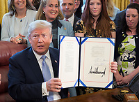 United States President Donald. J. Trump displays H.R. 1865, the &quot;Allow States and Victims to Fight Online Sex Trafficking Act of 2017&quot; after signing it into law at The White House in Washington, DC, April 11, 2018. With Trump are victims and family members of victims of online sex trafficking and members of Congress who helped pass the bill. <br /> CAP/MPI/CNP/RS<br /> &copy;RS/CNP/MPI/Capital Pictures