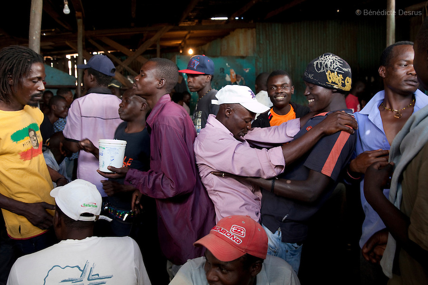 People dance and drink Busaa, a traditional fermented beer, at Madiaba Busaa club at midday in a Nairobi slum on April 14, 2013. Busaa is made by crudely fermenting maize, millet, sorghum or molasses. At Kshs 35 per liter it is much cheaper than a Kshs120 half-liter bottle of commercial beer. The local brew was legalised in 2010 and since then Busaa clubs have become increasingly popular in slums and rural areas. Drinking is on the rise in Kenya, especially among young people. Photo by Benedicte Desrus