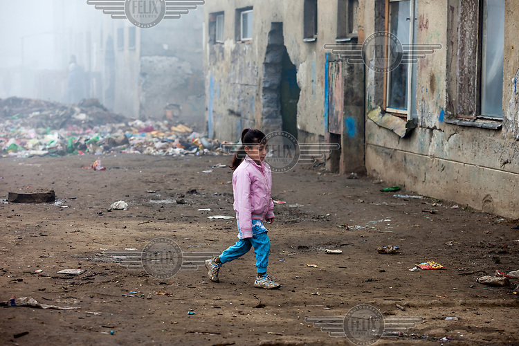 A young girl walks on a muddy patch of ground in the Roma settlement located in 'Budulovskej Street'.