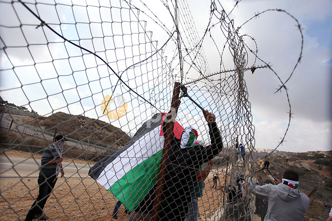 Palestinian youths cut a section of Israel's separation fence in the West Bank village of Ramat near Ramallah to protest against Israel's military action on the Gaza Strip, on November 19, 2012 . Israeli air strikes across the Gaza Strip killed 13 people, raising the Palestinian death toll to 90 as Israel's relentless air campaign entered its sixth day. Photo by Issam Rimawi