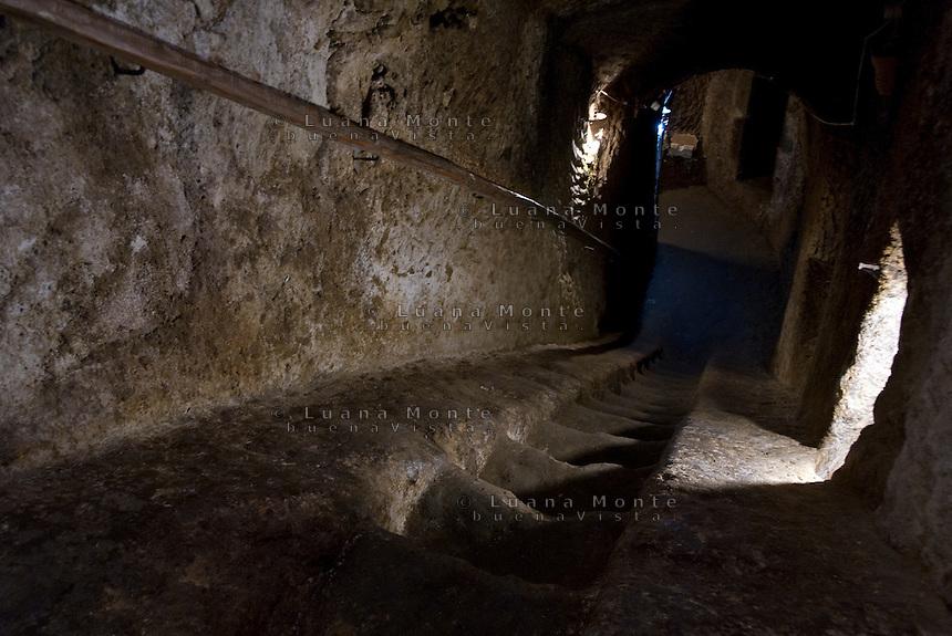 Civita di Bagnoregio. Una delle numerose cisterne per la raccolta dell'acqua piovana scavate dagli etruschi nello strato superiore del tufo della rupe. I loro ingressi oggi si aprono nei pavimenti al piano terra degli edifici e vengono ancora utilizzati come cantine.