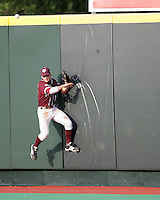 Texas A&M RF Brian Ruggiano collides with the wall on Texas Catcher Cameron Rupp's double on May 16th, 2008 in Austin Texas. Photo by Andrew Woolley / Four Seam images.