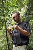 INDONESIA, Flores, writer and journalist Bernd Schwer eats some mango on the trail to Wae Rebo Villlage