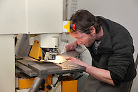 Staff member Eric Euzenat (1972-2016) perforating a sheet of metal in the workshop of the new Parc Zoologique de Paris or Zoo de Vincennes, (Zoological Gardens of Paris or Vincennes Zoo), which reopened April 2014, part of the Musee National d'Histoire Naturelle (National Museum of Natural History), 12th arrondissement, Paris, France. Picture by Manuel Cohen