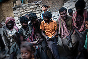 After a long days' work, miners gather to distribute the days wage in village Bokapahari in Jharia, Jharkhand, India. miners work for 9-10 hours a day and make Rs.150 ($3.5) a day loading the coal trucks in the BCCL coal mines in Jharia. Coal fires rage just below the surface of the ground, making it too hot to walk with naked feet, noxious gases spew up from fissures, making the environment toxic. Photo: Sanjit Das