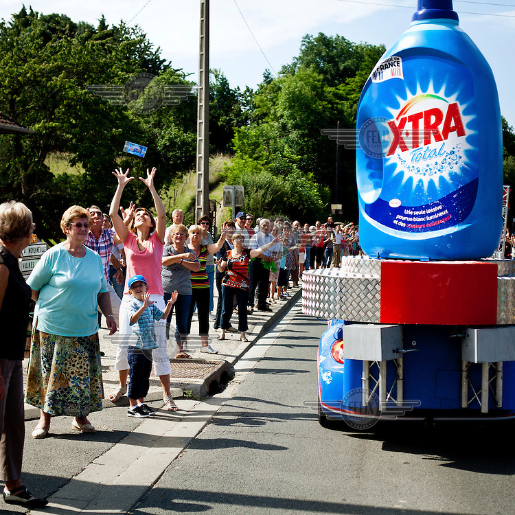 Excited spectators cheer and wave and are thrown free samples as the Tour de France Caravan passes by. This parade, consisting of cars advertising various brands and goods, travels ahead of the actual race, along the race route. According to official Tour de France website, this parade has become an essential part of the race and as many as 47% of spectators come first and foremost to see the caravan..