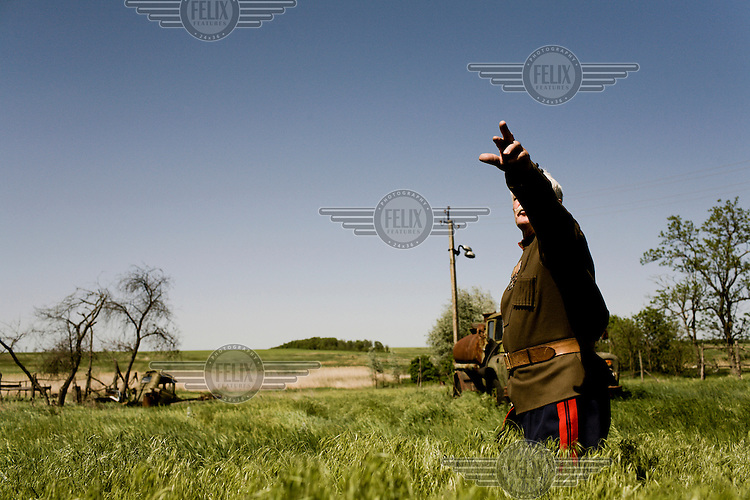 Cossack World War Two veteran Nikolai Abromovich stands in a field  outside his dacha (summer home) dressed in his army uniform.