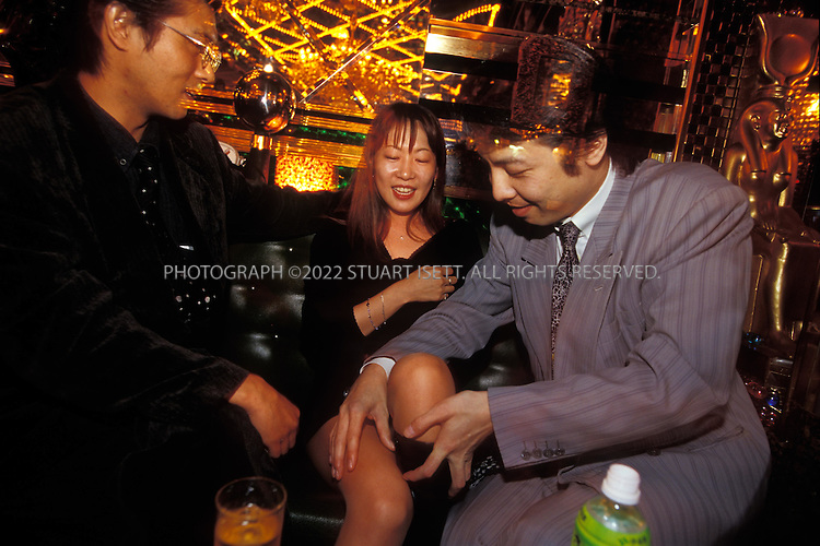 10/10/2002--Tokyo, Japan..Like hostesses, the male hosts main job is to entertain and relieve the daily stress of the client. Here a female client enjoys the company of 2 hosts, engaging in flirtatious talk and a touch without seeming too sexually aggressive...All photographs ©2003 Stuart Isett.All rights reserved.This image may not be reproduced without expressed written permission from Stuart Isett.
