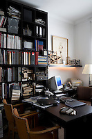 A wooden desk and shelving in a modern home office room