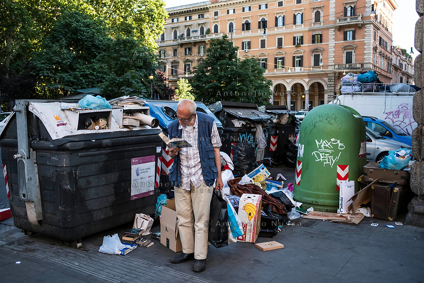 Rome, Italy, June 21, 2017. Un anziano signore legge un libro appena raccolto da un cumulo di rifiuti. An elder man reading a book picked up from the rubbish.<br /> Ad un anno dalla elezione a sindaco di Roma di Virginia Raggi, la condizione di degrado non accenna a migliorare.<br /> One year after the election as mayor of the candidate of M5S party, Rome is worsening day by day.