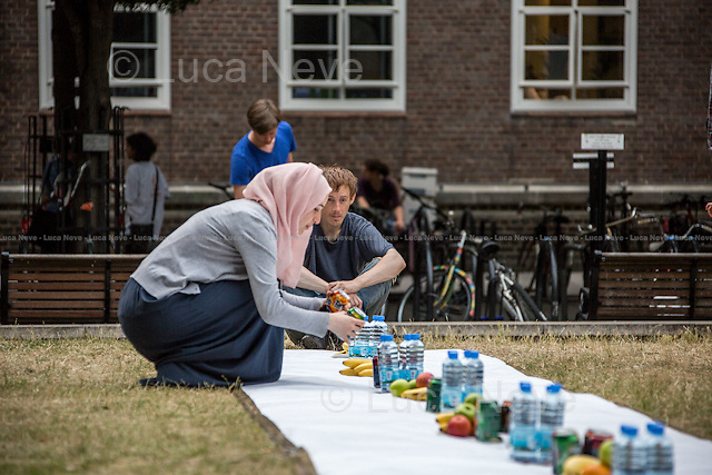 London, 17/07/2013. Students at the School of Oriental and African Studies (SOAS) share Iftar (the evening meal when Muslims break their fast during the month of Ramadan) with people in the holy month of Ramadan. Today, they were joined by Hassen Rasool, who spoke briefly about himself and how he became Channel 4's voice behind the Adhan (the Islamic call to prayer, recited by the muezzin at prescribed times of the day) Fajr (the first of the five daily prayers). After prayer they ate food provided by Somali Relief and Development Forum.