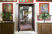 A view from the sitting room with paintings by South African artist Nicolaas Maritz into the kitchen. Traditional local materials were kept during the restoration of the house, such as the terracotta tiles on the floor.