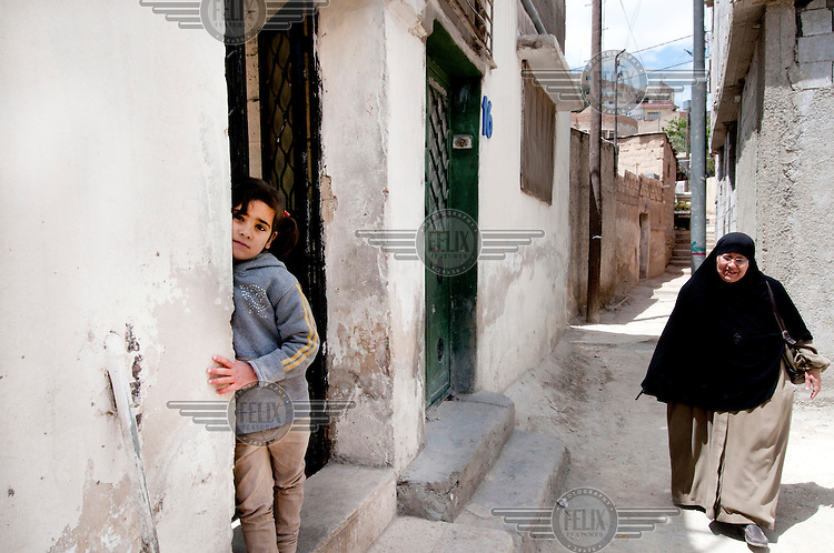 A young girl stands at the entrance of the home of her mother Samah, 24 and Darwish 34, refugees who fled the civil war in Syria. They have four children. /Felix Features