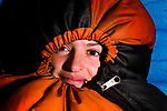 Andean Mountain Cat (Leopardus jacobita) biologist, Cintia Tellaeche, bundled up in sleeping bag, Loma Blanca, Abra Granada, Andes, northwestern Argentina