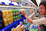 A woman picks up a can of Sapporo Breweries Ltd.'s popular Ebisu brand of beer at a supermarket in Tokyo, Japan.