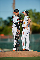 Baltimore Orioles relief pitcher Lucas Long (90) talks with catcher Austin Wynns (61) on the mound during a Grapefruit League Spring Training game against the Detroit Tigers on March 3, 2019 at Ed Smith Stadium in Sarasota, Florida.  Baltimore defeated Detroit 7-5.  (Mike Janes/Four Seam Images)