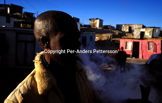 ditown00172 Township An unidentified man smoking mandrax from a broken beer bottle on August 12, 2001 in Site C Khayelitsha, a township about 35 kilometers outside Cape Town, South Africa. Khayelitsha is one of the poorest and fastest growing townships in South Africa. People usually come from the rural areas in Eastern Cape province to find work as maids and laborers. Most people don't find work and the unemployment rate is very high, together with lot of violence and a growing HIV-Aids epidemic itÕs a harsh area to live in. Drugs, bottleneck.Photo: Per-Anders Pettersson/iAfrika Photos.
