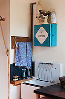 The old-fashioned utility room has a turquoise medicine cabinet with a large poison sign on it on the wall above the enamel sink