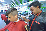 Yared Kifleyesus, a recent refugee from Eritrea, cuts the hair of Meeran Rahim in Harrisonburg, Virginia. Kifleyesus was resettled in Harrisonburg by Church World Service.<br /> <br /> Photo by Paul Jeffrey for Church World Service.