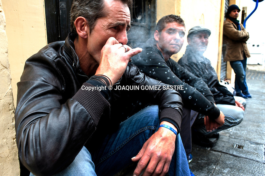 Uberto was born in Madrid  has recently become unemployed, smokes a cigarette while waiting for the row of faces in the Saint Nicolas Project consisting of a sandwich and a soda to give volunteers in Alicante.