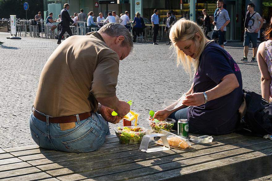 Nederland, Amsterdam, 16 juli 2015<br /> Amsterdam Zuidas.  Kantoorpersoneel op de Zuidas nuttigt buiten op een bank een meeneemmaaltijd<br /> <br /> Foto: Michiel Wijnbergh