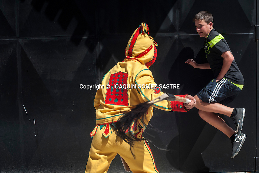 The colacho, burlesque pantomime representing the devil, whipping his zurriego (whip) to a boy being chased through the streets of Castrillo de Murcia (Burgos)