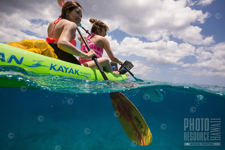 Young Japanese tourists kayaking on a beautiful sunny day in Makua Bay
