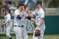California Baptist University Lancers starting pitcher Justin Montgomery (22) is greeted by a teammate after an inning against the Concordia Eagles at James W. Totman Stadium on March 31, 2018 in Riverside, California. The Lancers defeated the Eagles 6-2.  (Donn Parris/Four Seam Images)