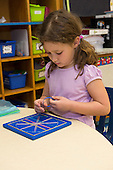 MR / Schenectady, NY. Zoller Elementary School (urban public school). Kindergarten inclusion classroom. Student (girl, 5) does manipulative activity with rubber bands and geoboard during math learning center time. MR: Cas12. ID: AM-gKw. © Ellen B. Senisi.