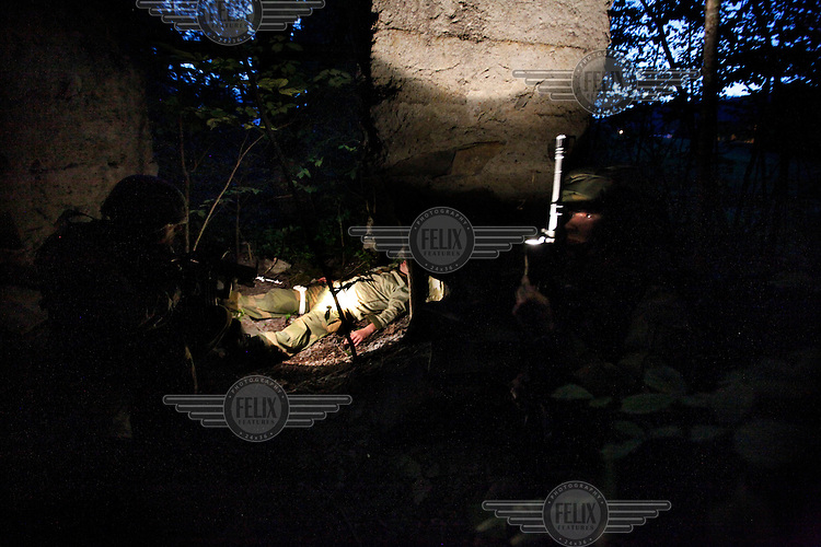Soldiers find a wounded man in the forest at night. Norwegian Home Guard soldiers during exercise Djerv..The Home Guard has traditionally been designated to secure important  domestic installations in case of war or crisis. With the cold war long gone, a war in Afghanistan and budget cuts, there is a debate over the Home Guard's role in the future.