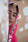 Rajasthani dancer wearing make-up and traditional jewelry looking out of hut door, Thar Desert, Rajasthan, India --- Model Released
