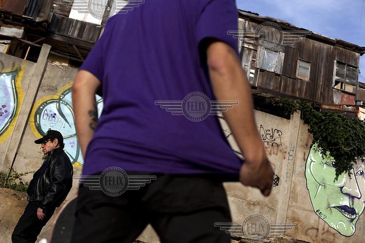 Men walk past graffiti covered walls below shacks made of coregated iron.