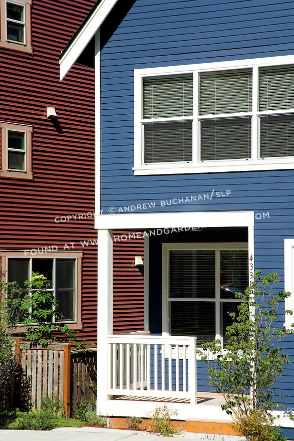 Detail of a royal blue, new construction townhouse with a small, white-painted front porch and trim sits adjacent to a deep red home in this contemporary urban development in Seattle.