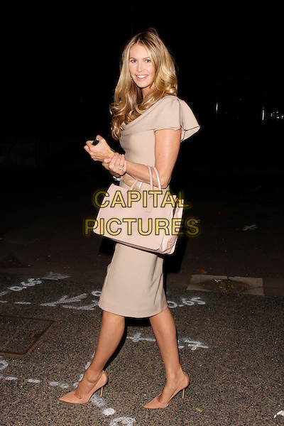 Elle Macpherson.Calvin Klein and John Pawson - private dinner arrivals, The New Design Museum, London, England..October 13th, 2011.full length beige pink nude dress shoes bag purse side .CAP/AH.©Adam Houghton/Capital Pictures.