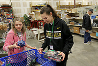 NWA Democrat-Gazette/DAVID GOTTSCHALK  Ela Kisor (right), a junior at Fayetteville High School, and Kelsey Brewer, a senior, sort items Wednesday, March 13, 2019, for shelving at the Habitat for Humanity ReStore of Washington County in Fayetteville. The students are in the Fayetteville High School Ambassadors Service Learning Program and volunteer during school hours at the store. The class also requires an additional 25 hours of community service outside of school hours per semester. The ReStore is open Tuesday through Saturday.