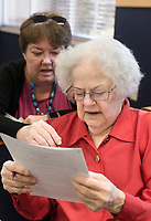 NWA Democrat-Gazette/CHARLIE KAIJO Mary Neal, Notary Public, (right) and Judi Frigon (left) go over paper work candidate filing paperwork, Monday, November 4, 2019 at the Benton County Administration Building in Bentonville.