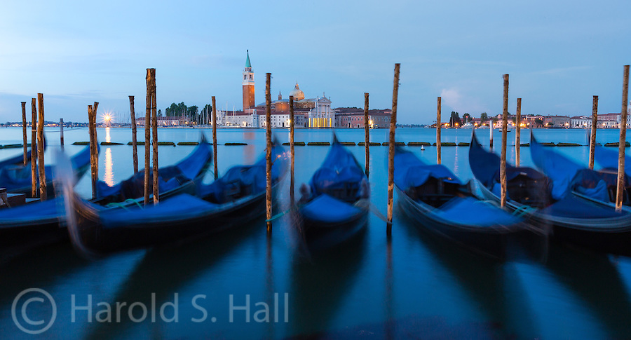 The famous gondolas of Venice, Italy rock in the waves from other passing boats.  Soon they will be paddling excited tourists along the narrow canals.