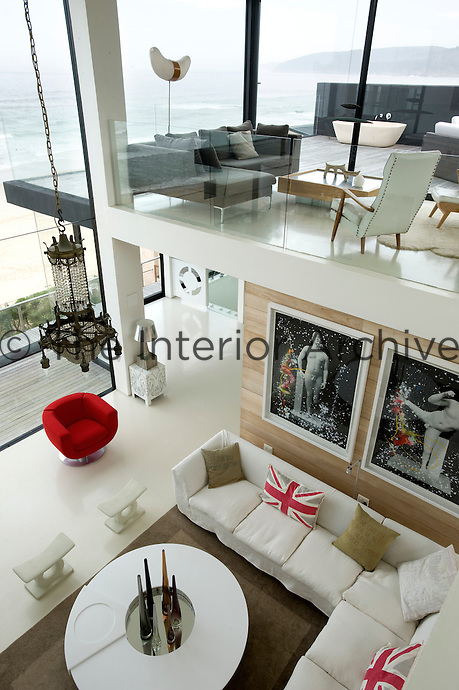 Looking down from the mezzanine to the open plan living area below which is furnished with modern art and white furniture
