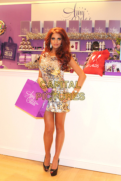 Amy Childs .Opens Her New Clothes Boutique At Eastgate Shopping Centre, Basildon, Essex, UK, 1st December 2012..full length dress mini silver sequined sequin black platform peep toe shoes purple shopping store bag hand on hip .CAP/BRC.©Ben Rector/Capital Pictures.