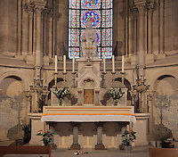 Apse in the choir with altar laid with flowers and candles and statue of the Virgin and child, in the Collegiale Notre-Dame de Poissy, a catholic parish church founded c. 1016 by Robert the Pious and rebuilt 1130-60 in late Romanesque and early Gothic styles, in Poissy, Yvelines, France. The nave was reworked in the 15th and 16th centuries and has bays on both sides leading to the side aisles. Saint Louis was baptised here in 1214. The Collegiate Church of Our Lady of Poissy was listed as a Historic Monument in 1840 and has been restored by Eugene Viollet-le-Duc. Picture by Manuel Cohen