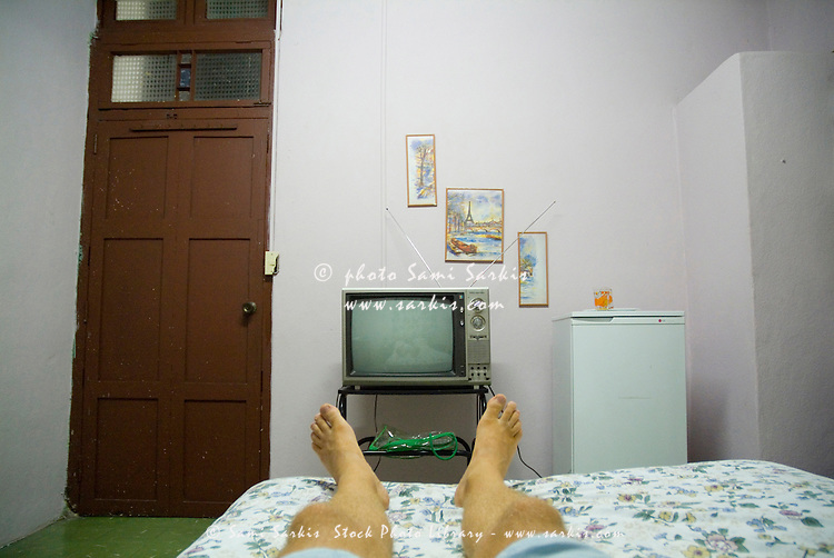Man's legs on a bed in front of an old TV at a guesthouse, Santa Clara, Villa Clara, Cuba.