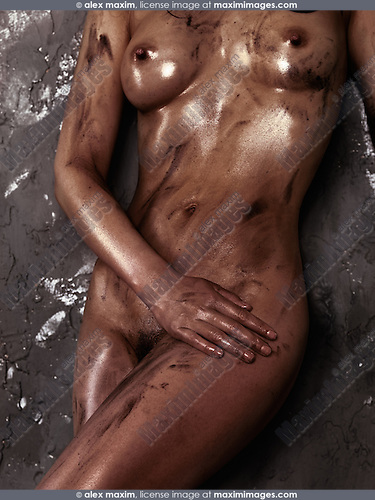 Beautiful young naked woman body with shiny soiled black skin leaning against a rustic wall
