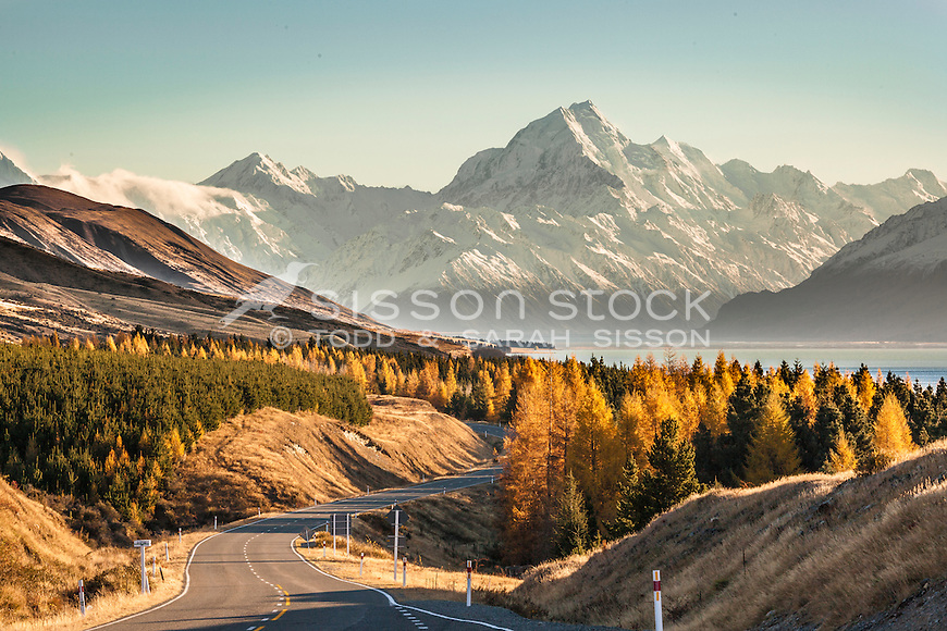 A winding road leads to Mount Cook looming above Lake Pukaki in the early morning