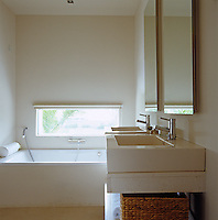 The rectangular window above the bath in the master bathroom has views across the garden