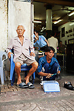 VIETNAM, Saigon, restaurant Pho Hoa aka Pho Hoa Pasteur, the owner sits in a chair relaxing while a young man polishes restaurant customers shoes, Ho Chi Minh City VIETNAM, Saigon, restaurant Pho Hoa aka Pho Hoa Pasteur, the owner sits in a chair relaxing while a young man polishes restaurant customers shoes, Ho Chi Minh City