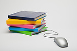 Stack of colorful books and computer mouse